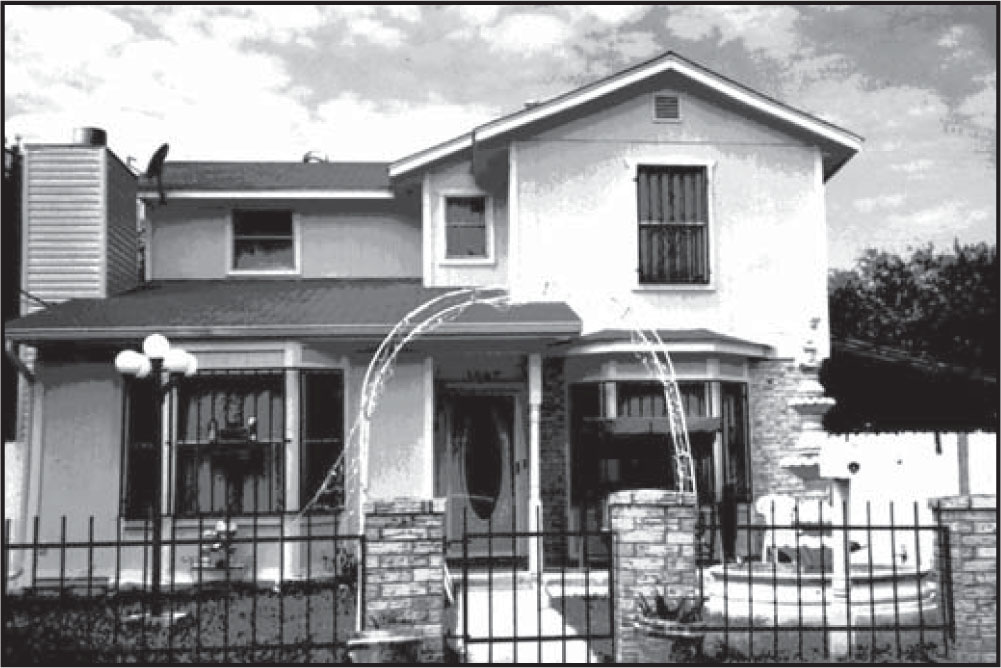 Photograph of a house with bars on the windows.